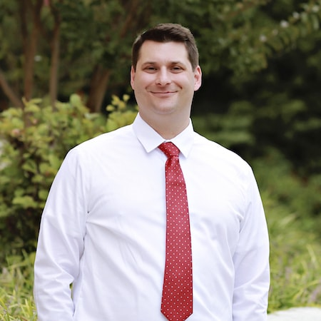 Charlottesville Dental Team manager, Adam Schulz smiling and wearing a red tie